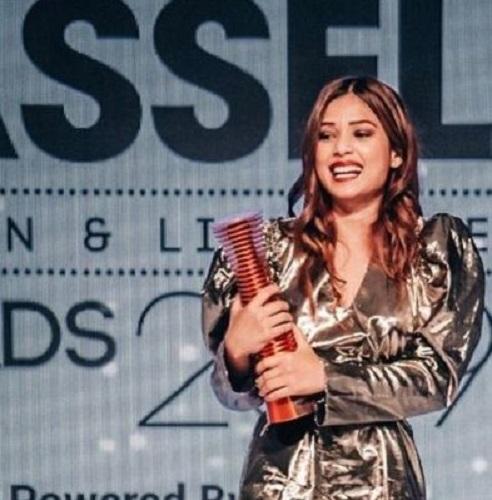 Riya Jain receiving an award