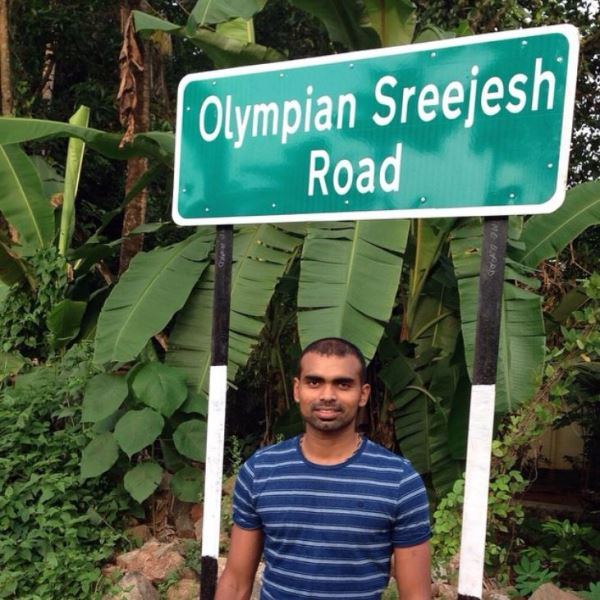 P. R. Sreejesh standing under the signboard mentioning a route with his name