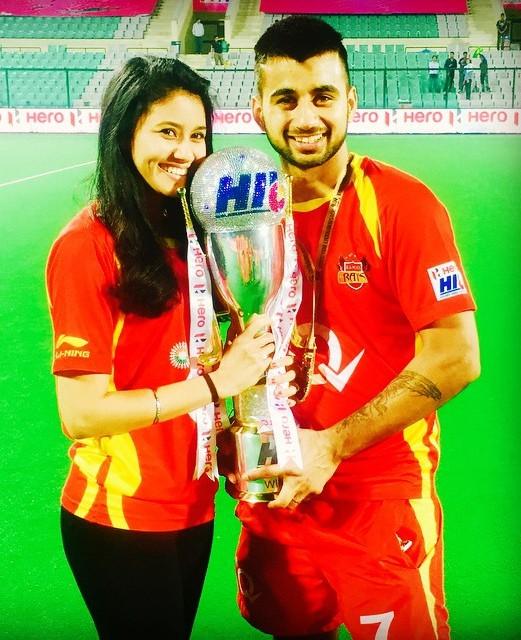 Manpreet Singh posing with the Hero Hockey India League trophy, along with Illi Najwa Saddique